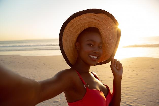 Donna felice in cappello che sta sulla spiaggia