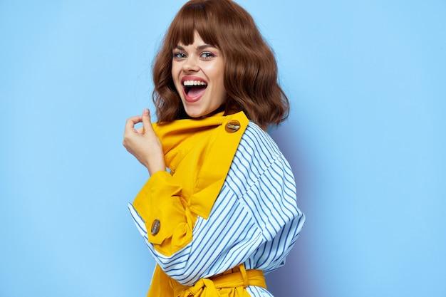 Donna felice in cappotto con gesti di bocca spalancata con le mani sul blu