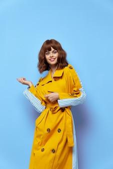 Donna felice in cappotto giallo con maniche a righe mostra con la mano a lato sul blu