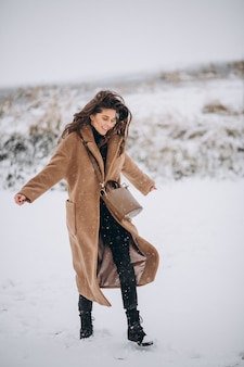 Donna felice in cappotto in inverno fuori nel parco
