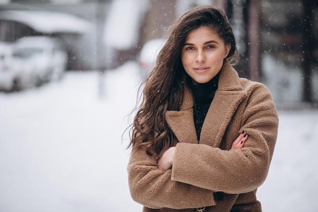 Donna felice in cappotto in inverno fuori