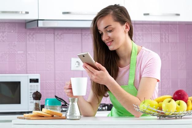 Donna felice in chat online e bere caffè caldo e gustoso per la colazione al mattino presto in cucina a casa. online, dipendenza da telefono