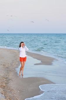 Donna felice in maglietta bianca e pantaloncini rossi in piedi vicino al mare su una spiaggia.