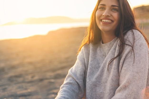Donna felice in maglione che si siede sulla riva del mare sabbioso