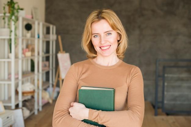 Donna felice in piedi con il libro