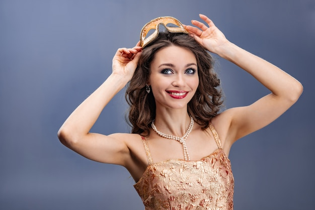 Donna felice in un abito d'oro e collana di perle che indossa una maschera di carnevale sopra la sua testa