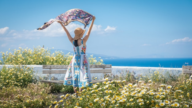 Donna felice in un bel vestito con fiori. campo con margherite.