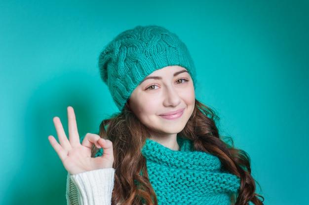 Donna felice in un cappello lavorato a maglia turchese in studio