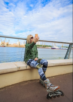 Donna felice nei pattini di rullo che si siedono e che fanno la foto del selfie sullo smart phone sulla riva del fiume