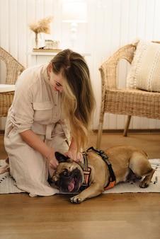 Donna felice nel rimorchio che gioca con il cane, durante il viaggio e il campeggio, divertendosi
