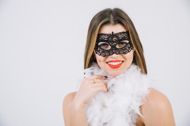 Donna felice nella piuma di boa da portare della mascherina di carnevale su priorità bassa bianca