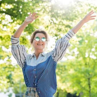 Donna felice nella vista frontale del parco di estate