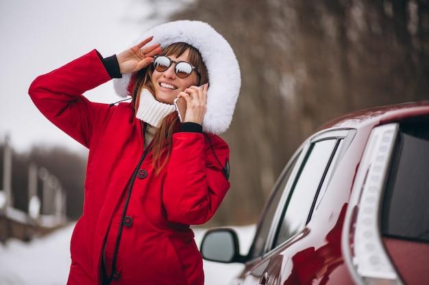 Donna felice parlando al telefono fuori in auto in inverno