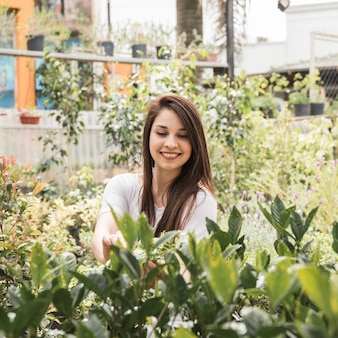 Donna felice prendersi cura delle piante in serra