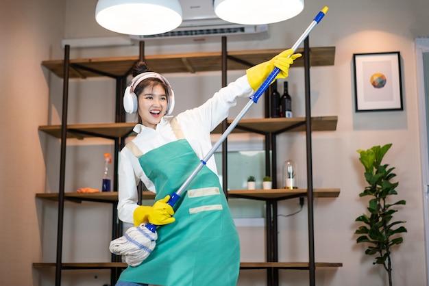 Donna felice pulizia casa con scopa e divertirsi