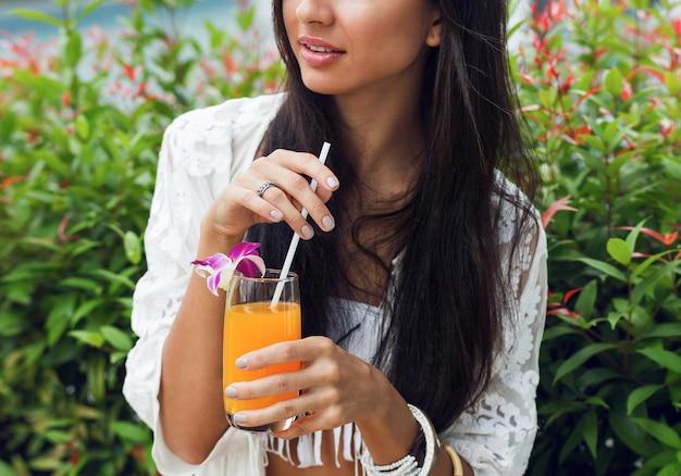 Donna felice rilassante con gustoso succo d'arancia fresco in abito tropicale boho alla moda durante le sue vacanze.
