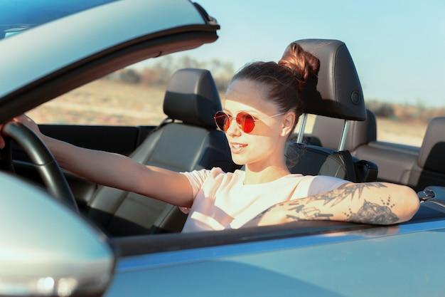 Donna felice rilassata che viaggia in automobile
