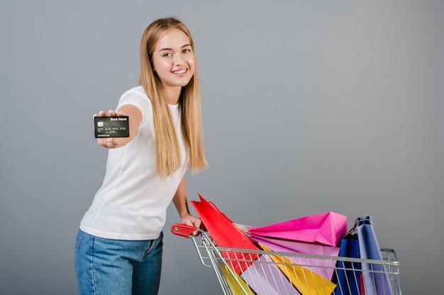 Donna felice sorridente con la carta di credito e carretto a mano con i sacchetti della spesa variopinti isolati sopra grey