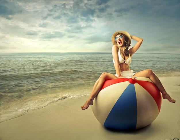 Donna felice su un enorme pallone da spiaggia