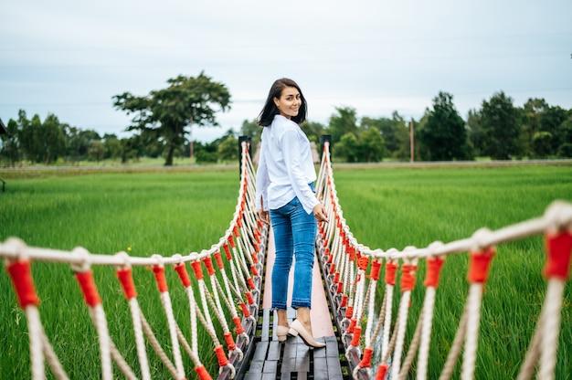Donna felice su un ponte di legno in un prato verde in una giornata di sole