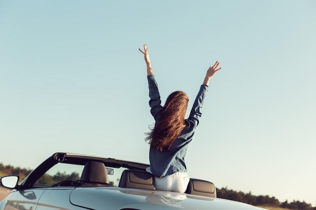 Donna felice viaggiatore in auto cabrio