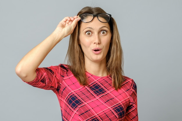 Donna femminile abbastanza caucasica impressionata senza parole con gli occhiali