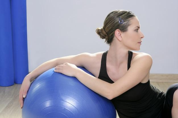 Donna fitness aerobica rilassata con palla blu stabilità pilates