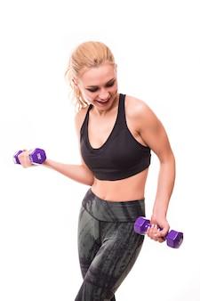 Donna fitness con i capelli biondi, lavorando con manubri