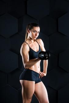 Donna fitness con manubri facendo un esercizio