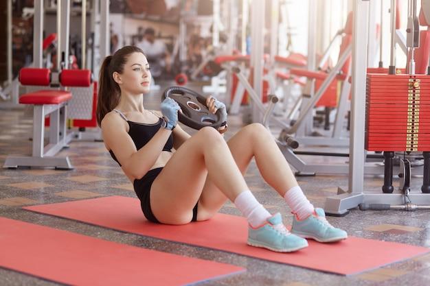 Donna fitness fotografata durante il suo allenamento in palestra. donna muscolare che si siede sulla stuoia sul pavimento che fa esercizio dell'abs con il piatto pesante, indossando cima e breve nere.