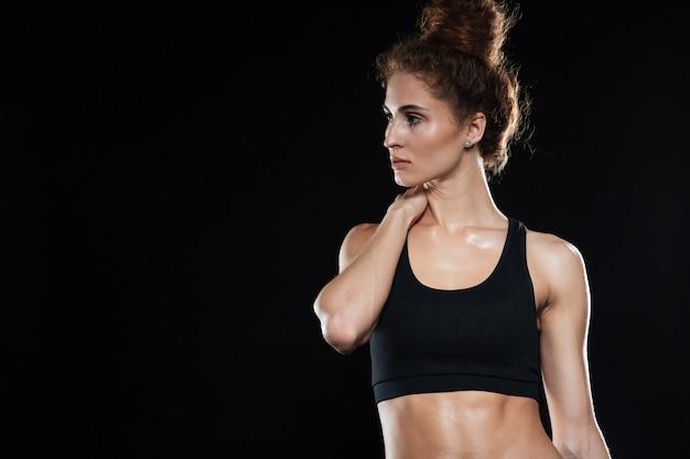 Donna fitness in piedi e tenendo il collo