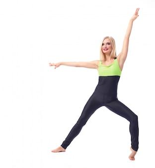Donna fitness in posa con grazia su bianco