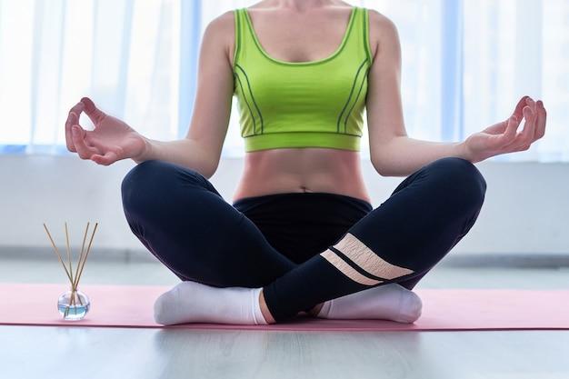 Donna fitness in posa di loto con bastoncini di aroma e bottiglia di olio essenziale sul tappetino durante la pratica dello yoga, trattamenti di aromaterapia e meditazione. salute mentale