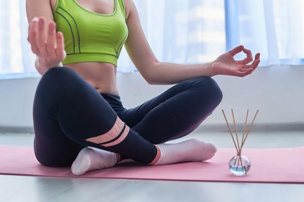 Donna fitness indossando abbigliamento sportivo nella posizione del loto con bastoncini di aroma e bottiglia di olio essenziale sul tappetino durante l'allenamento yoga, aromaterapia e meditazione. salute mentale