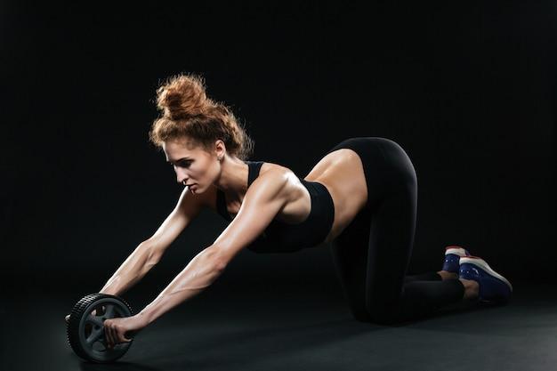 Donna fitness utilizzando la ruota di esercizi