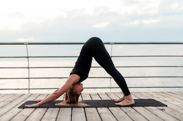 Donna flessibile che fa asana yoga vicino al mare all'alba al mattino, praticando esercizi di fitness e sport