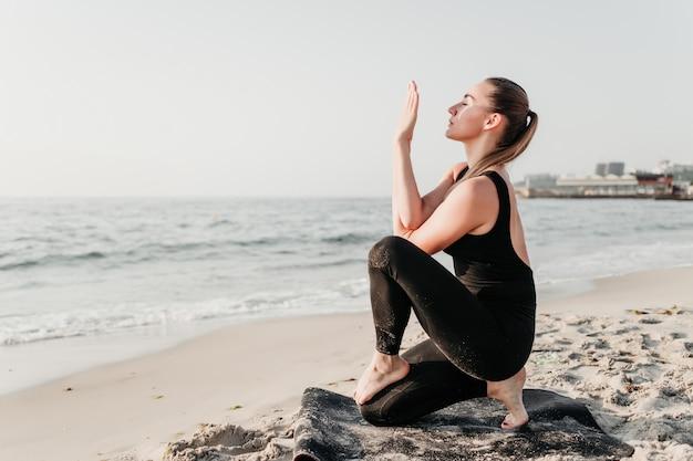 Donna flessibile che fa esercizio di forma fisica di yoga sulla sabbia vicino all'oceano
