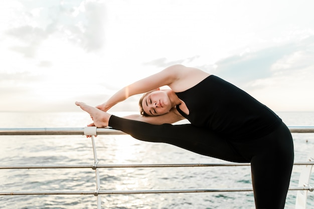 Donna flessibile che fa yoga asana vicino al mare all'alba del mattino, praticando sport e esercizi di fitness