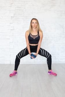 Donna forte che fa esercizio con le teste di legno