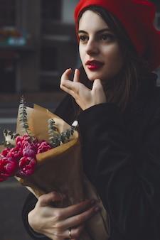 Donna francese con baguette sulla strada nel berretto
