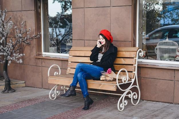 Donna francese in un berretto rosso su una panchina