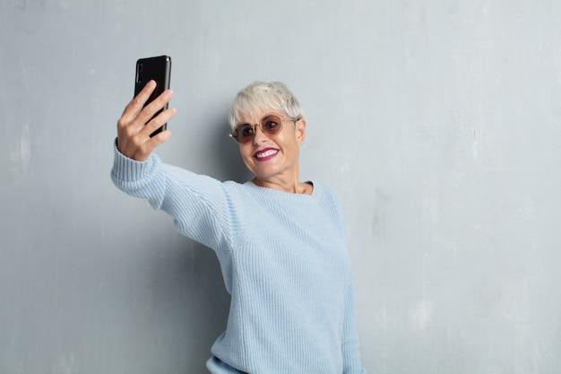 Donna fredda senior con uno smart phone contro la parete del cemento di lerciume