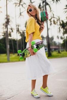 Donna fresca hipster con skateboard e cappuccio in posa sorridente in vacanza