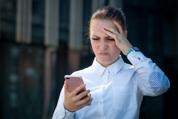 Donna frustrata esaurita frustrata triste, ragazza che esamina il suo telefono cellulare astuto delle cellule