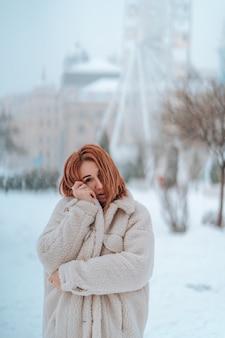 Donna fuori il giorno di inverno freddo di nevicata