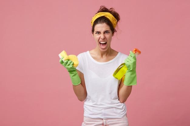 Donna furiosa e infastidita con sciarpa gialla sulla testa e guanti verdi in possesso di lavaggio spay e spugna con sguardo arrabbiato mentre sta per fare le pulizie di primavera. faccende domestiche, pulizie e riassetto