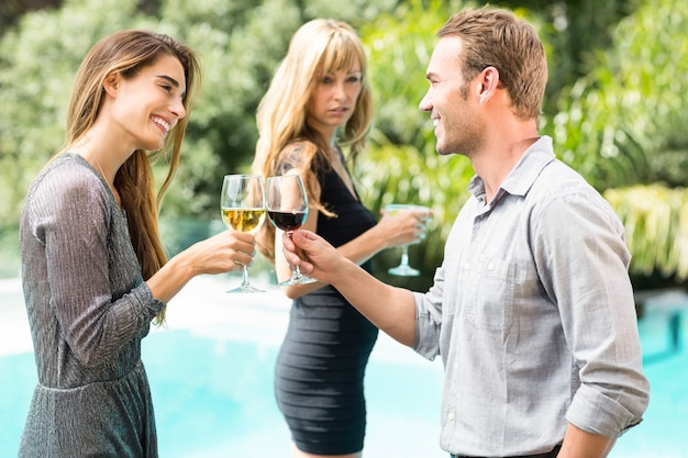 Donna gelosa che esamina coppie felici che tostano vino