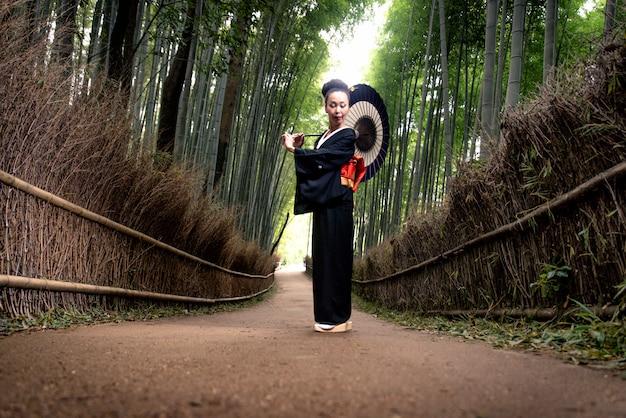 Donna giapponese con kimono nella foresta di bambù di arashiyama