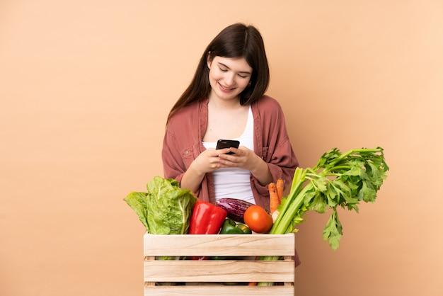 Donna giovane agricoltore con verdure appena raccolte in una scatola di invio di un messaggio con il cellulare