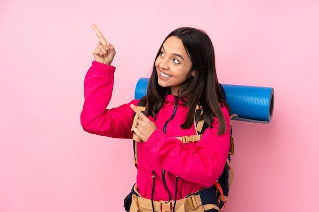 Donna giovane alpinista con un grande zaino che punta con il dito indice una grande idea